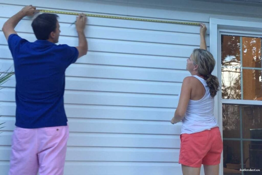 Couple measuring for an outdoor movie screen that will hang on the outside of their home when in use shown with measuring tape.