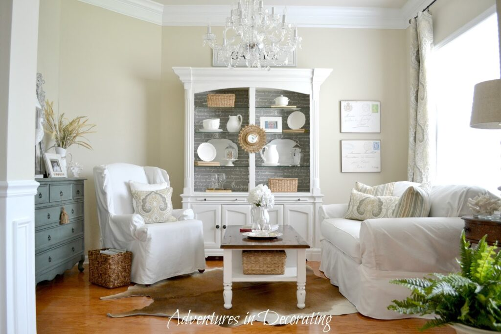 Brightly light sitting room featuring a white china cabinet, loveseat, and chair amidst light tan painted walls.