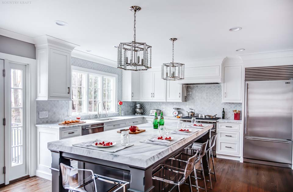 A large island in a kitchen space painted in Benjamin Moore's Wrought Iron, featuring a thick white and gray marbled countertop.