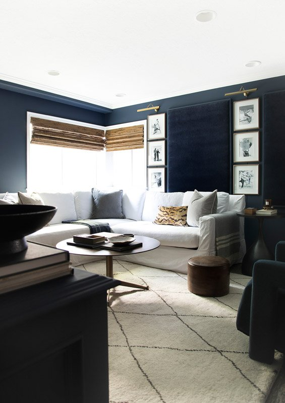 Dark blue painted walls in a living room with tan and brown natural decor.