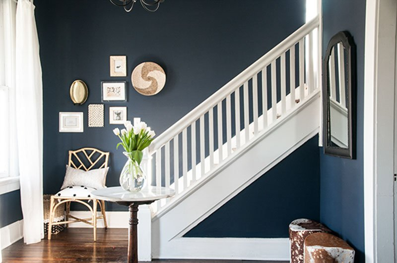 A classic white staircase of a home with a Sherwin Williams Naval blue wall leading upstairs.