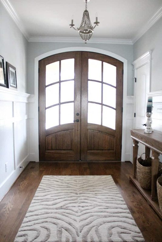 Dark wooden front doors in an entryway of a home with blue gray walls.