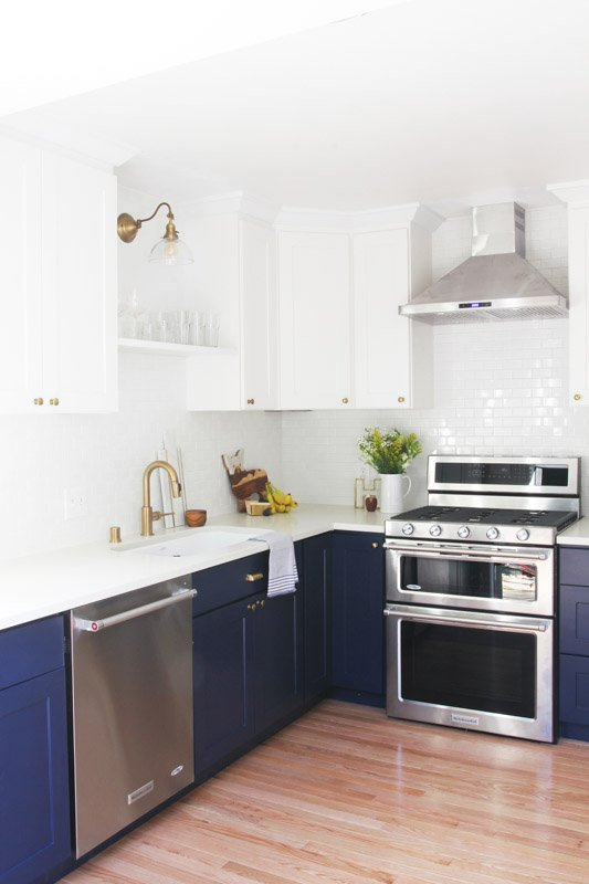 Lower cabinets painted Sherwin Williams Naval with stainless steel appliances and gold hardware,