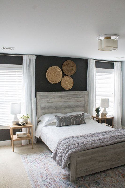 A cozy bedroom space with dark gray brown walls and light brown decor