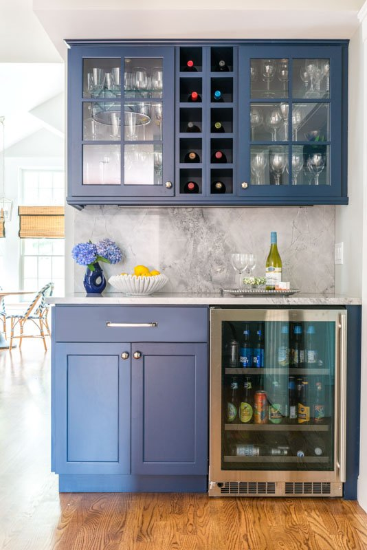 Navy blue painted kitchen cabinetry featuring a wine cooler and cabinets.