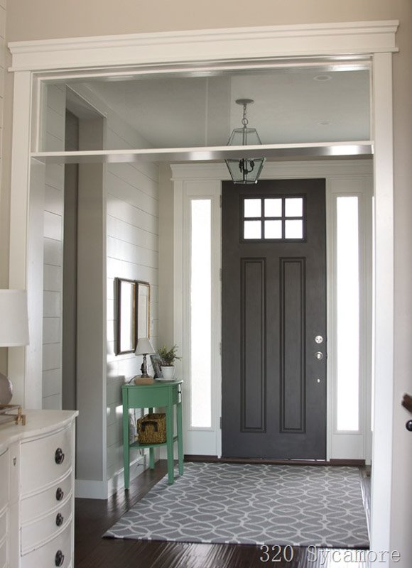 An entryway of a home featuring a tall front door painted in SW urbane bronze