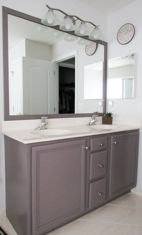 Soft gray walls of a bathroom against a darker vanity and mirror above