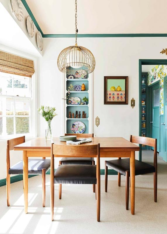 modern dining area with built in shelving and a table and chairs