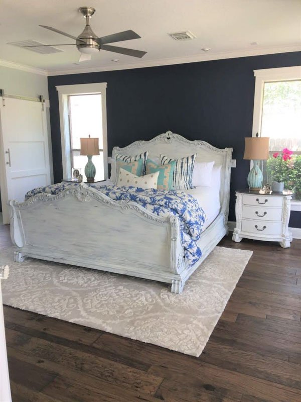 master bedroom with white wooden bed frame, side tables and navy painted walls.