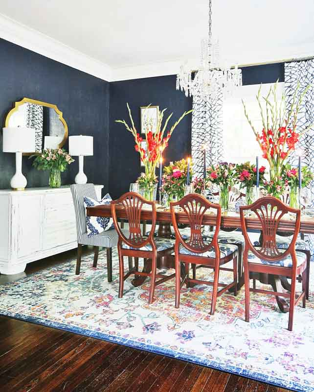 A dining room with naval walls and floral arrangements displayed on a wooden dining table