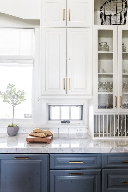 A kitchen with off-white upper cabinets and darker lower cabinets