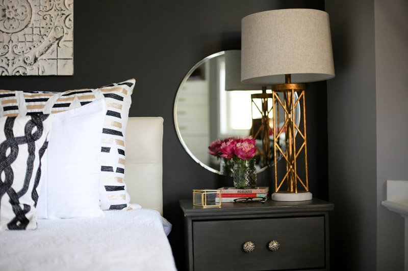 a dark painted side table beside a bed with white linens.
