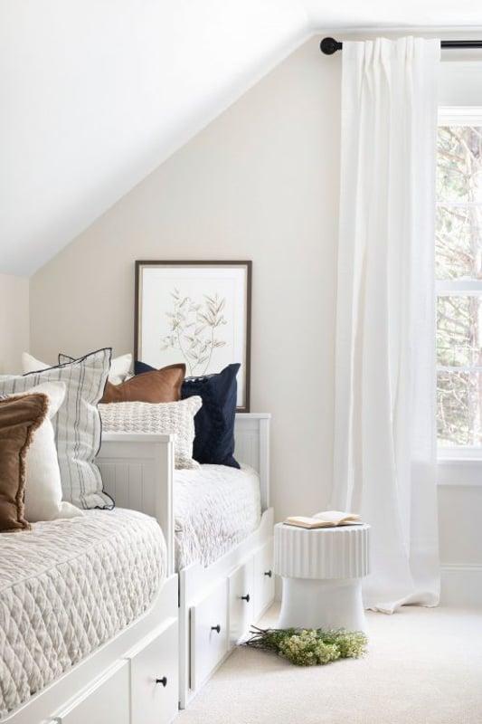 sun shining through a bedroom window of a room painted in benjamin moore swiss coffee