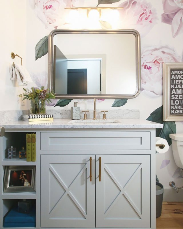Bathroom vanity painted in sherwin williams silvers strand, with a gold framed mirror above.