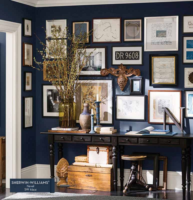 accent wall painted dark navy covered in gallery wall style framed art