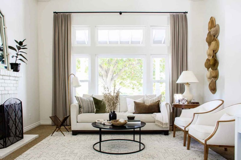 A living room painted in Benjamin Moore's Swiss Coffee, with tall curtains hung behind a classic sofa.