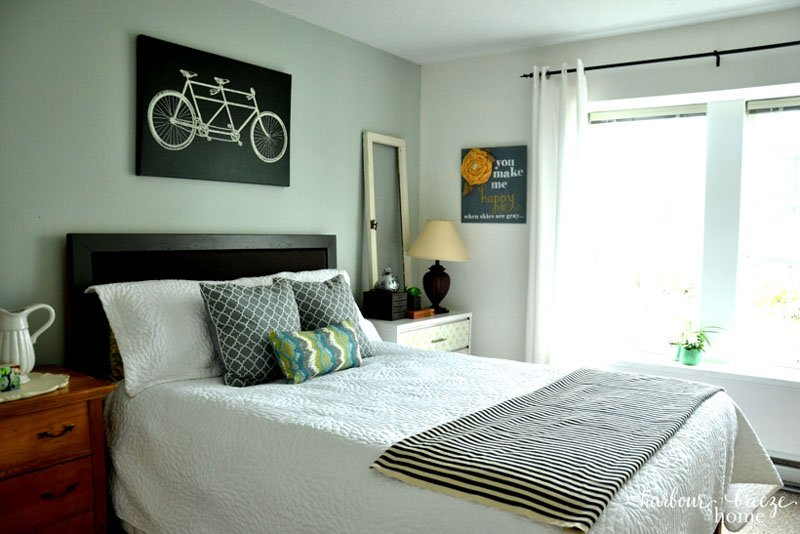 Bicycle wall art on gray walls above a full sized bed.