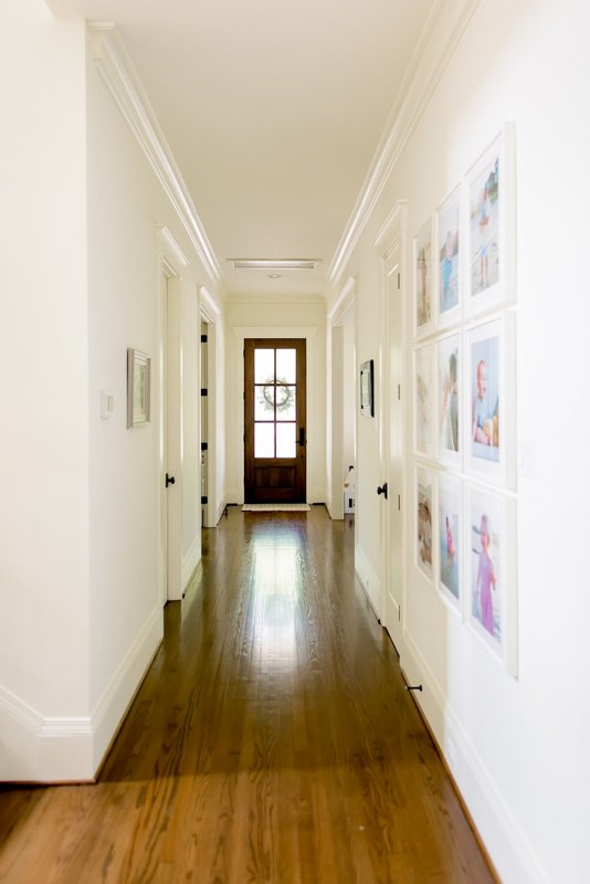 bright off-white hallway with a door at the end
