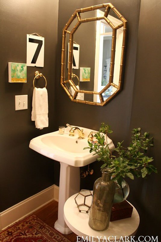 a small powder room with dark painted walls, white pedestal sink and gold mirror.