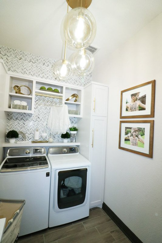 Walls and cabinetry in a small laundry room painted Sherwin Williams City Loft