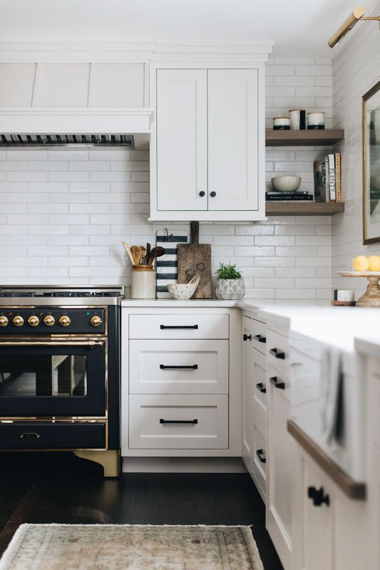 A kitchen with white subway tile backsplash and white painted cabinets