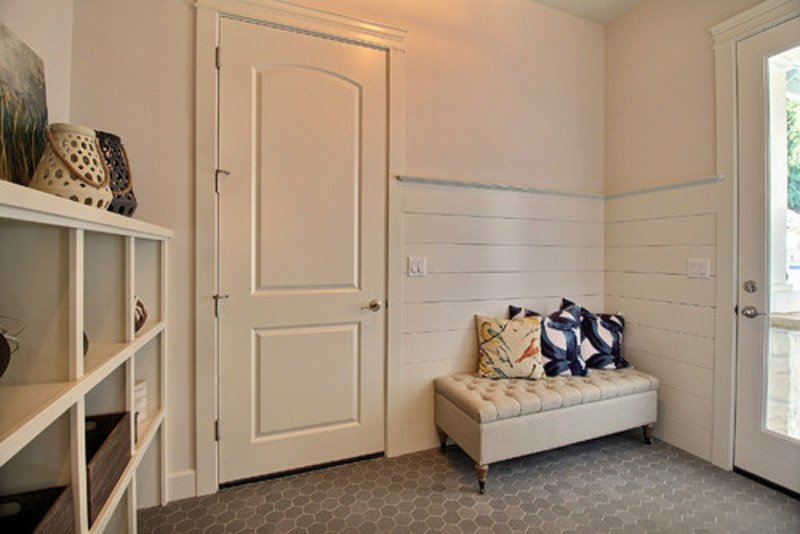 a mudroom with a bench, shelves and shiplapped wall with city loft paint