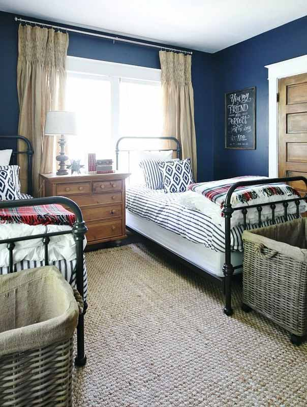 A bedroom with two twin beds, white and blue bedding, brown curtains and decor against Sherwin Williams Naval walls.