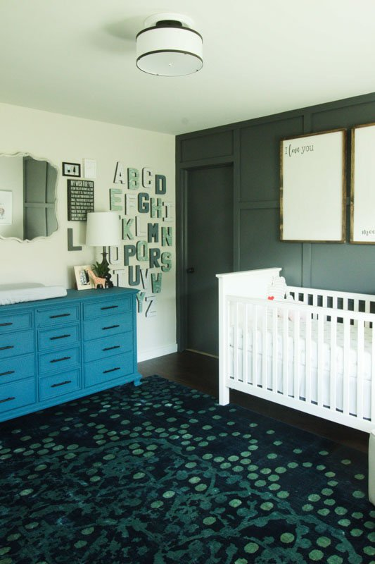 Infant's nursery with a dark accent wall and light gray adjacent walls