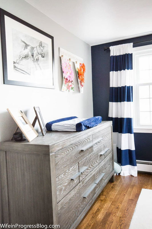 A dark blue accent in a boys nursery, with complimentary blue and white striped curtains.