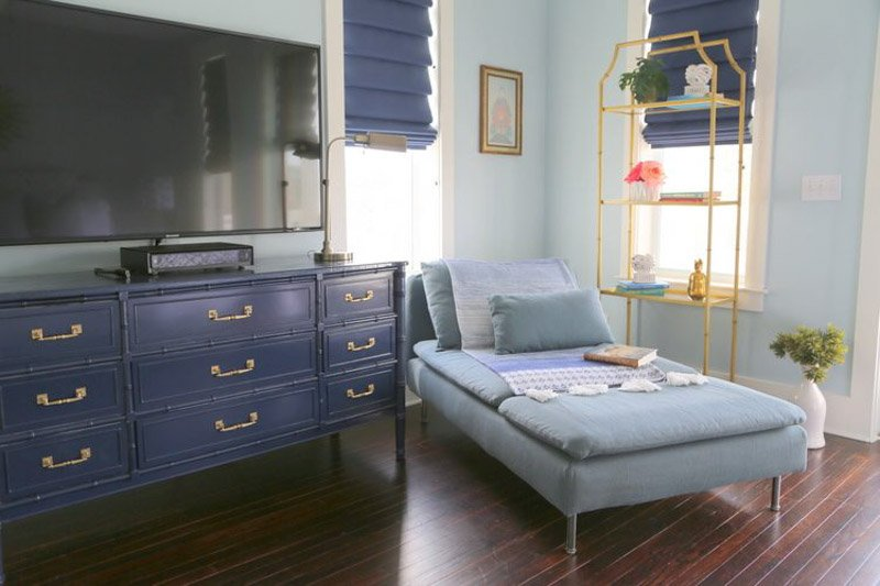 A small living area with a chaise lounge next to a repainted dresser turned TV stand in Naval paint.