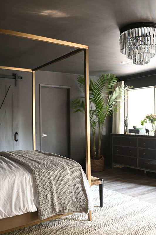 A chic master suite with monochromatic dark gray brown walls, doors and trim.