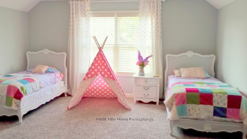 Two twin beds and a polkadotted teepee in a girl's silver painted bedroom.