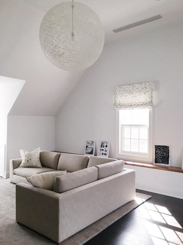 Living room with a neutral colored sectional and swiss coffee walls