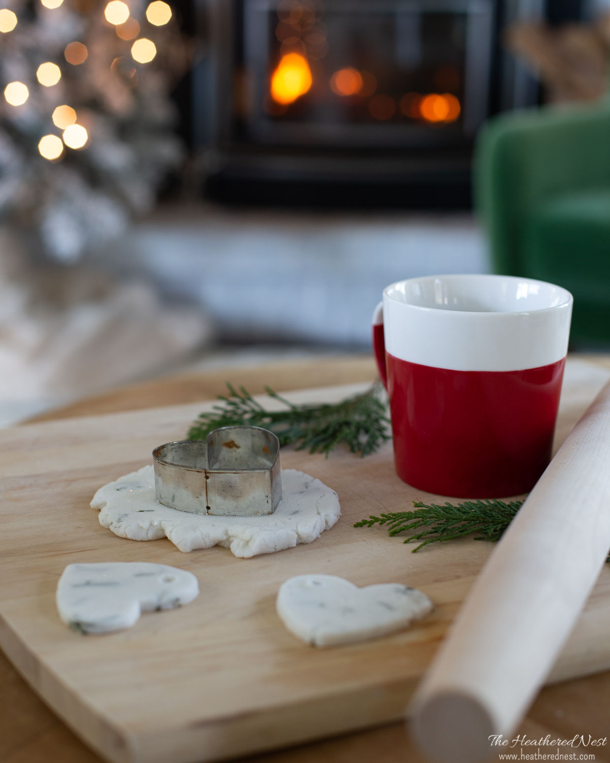 cutting heart shaped salt dough ornaments with a cookie cutter on a wood cutting board with wood rolling pin and cup of coffee by a fire and christmas tree
