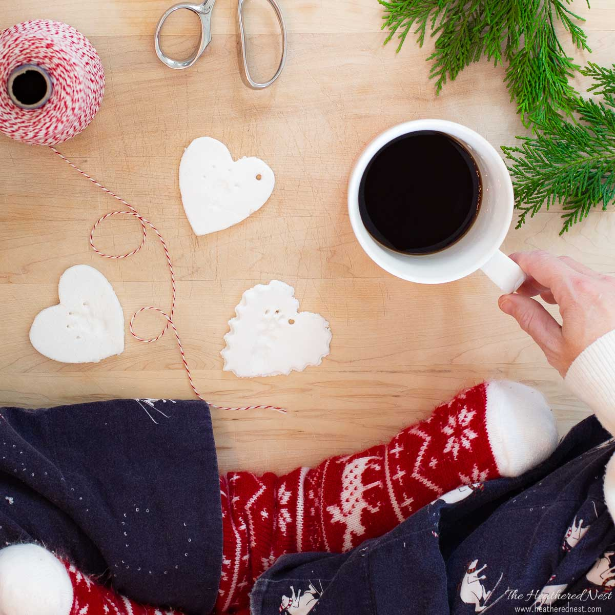 woman sitting cross-legged in Christmas pjs by a wood cutting board with three salt dough ornaments in heart-shapes. Also pictured butcher's twine, scissors and a cup of coffee