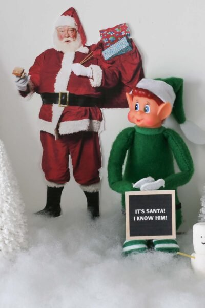 """elf doll dressed in green sitting in snow next to a printable Santa with letterboard sign """"It's Santa! I know him"""" and next to a marshmallow snowman sidekick"""
