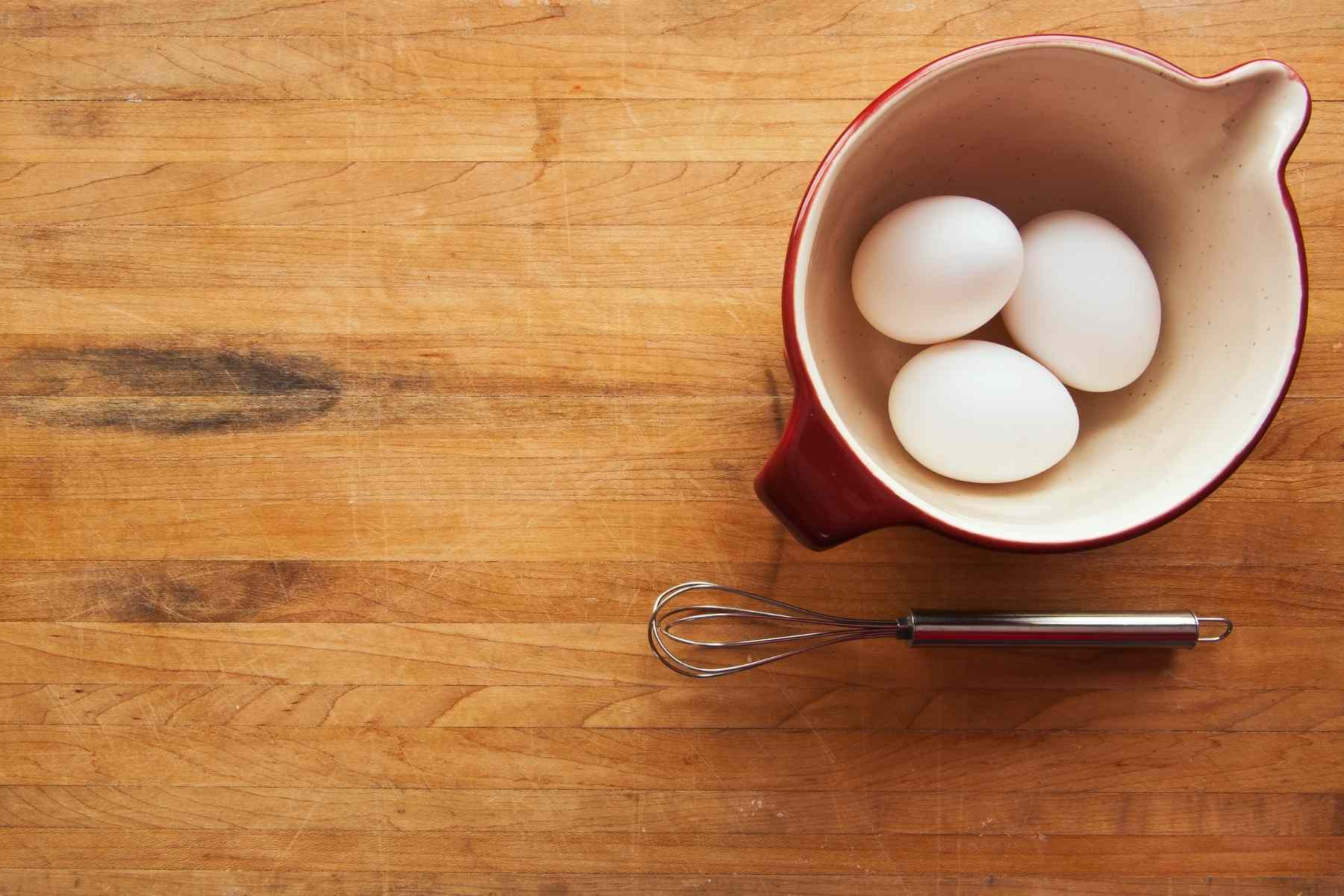 three eggs in a pitcher with a whisk on butcher block countertop