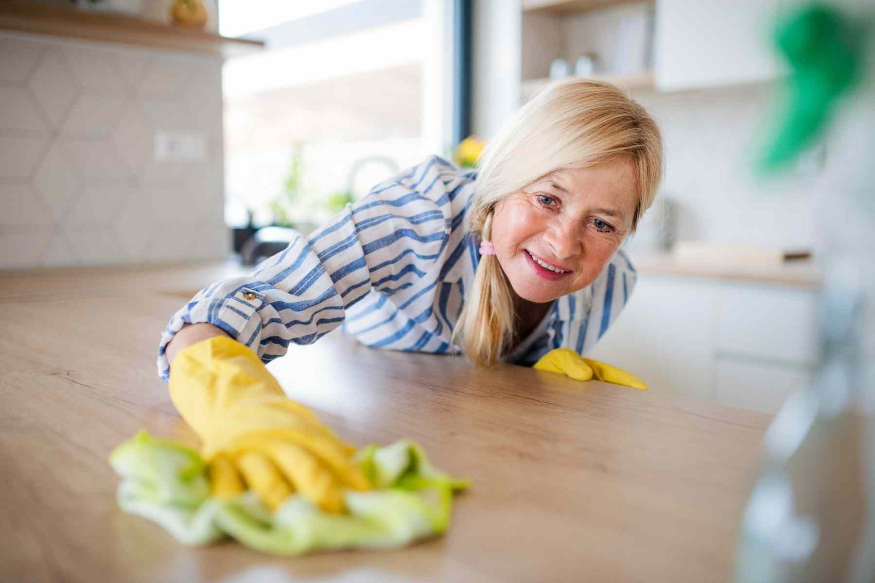 woman cleaning a wood countertop in a kitchen