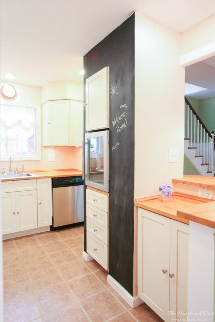 IKEA Karlby butcher block countertops in a historic townhome kitchen with stainless appliances and white cabinets; wine fridge and chalkboard wall