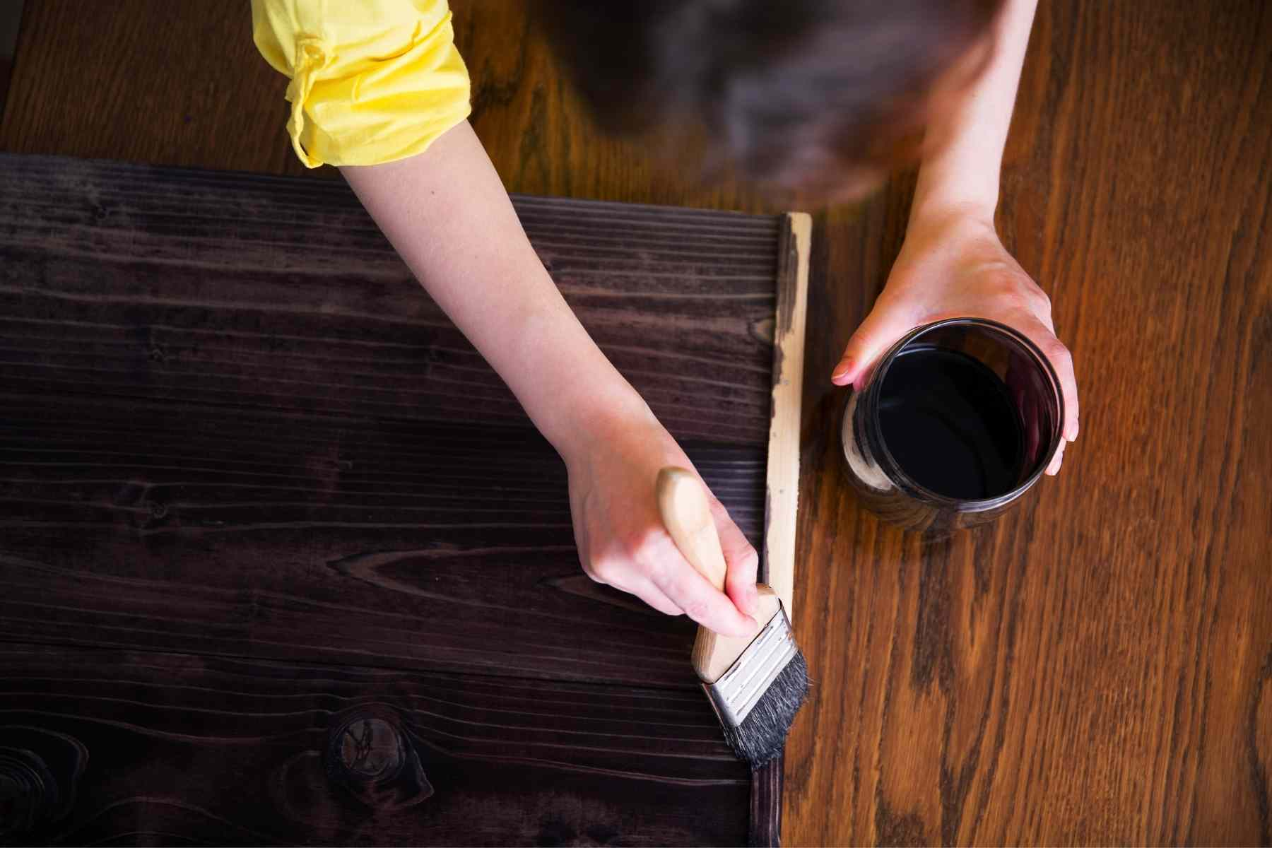person staining a piece of wood countertop